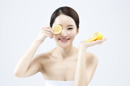 Asian beautiful woman with slice lemon isolated on white