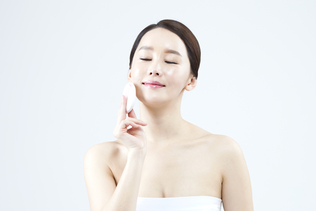 Asian beautiful woman applying powder isolated on white