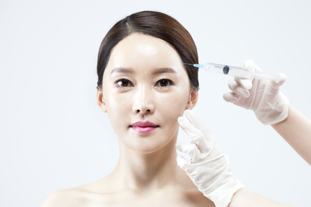 Asian beautiful woman at plastic surgery with syringe isolated on white