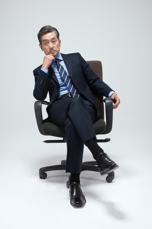 Asian man in suit on chair isolated on white Stock Photo