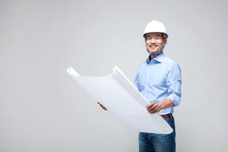 Aziatische die menseningenieur met blauwdruk op wit wordt geïsoleerd