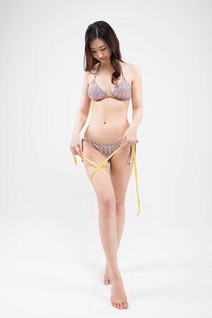 Asian woman in bikini measuring thigh isolated on white Stock Photo
