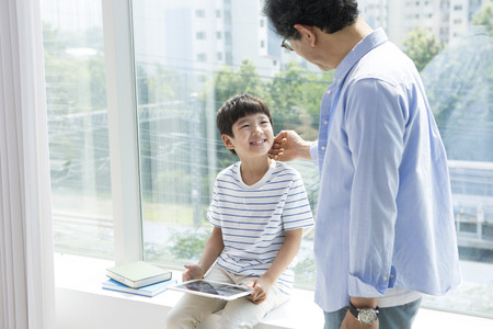 Asian grandfather and grandson using tablet pc