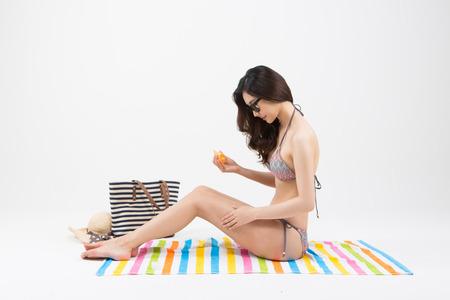 Asian woman in bikini applying sun block isolated on white Stock Photo