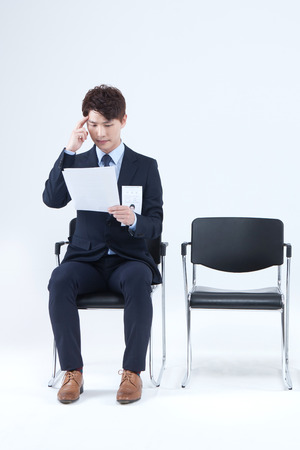 Asian man in suit waiting job interview isolated on white