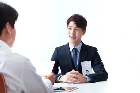 Hombre asiático en traje que tiene entrevista de trabajo aislada en blanco