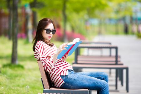 Asian beautiful woman reading book on bench