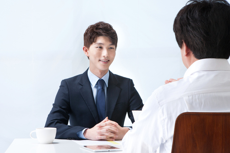 Asian man in suit talking with partner isolated on white