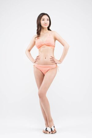 Asian woman in bikini posing isolated on white Stock Photo
