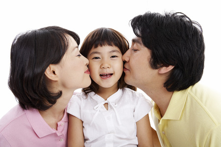 Asian parents kissing on their little daughters cheeks - isolated on white Stock Photo