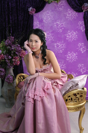 Young Asian woman in a pink dress posing in a vintage room