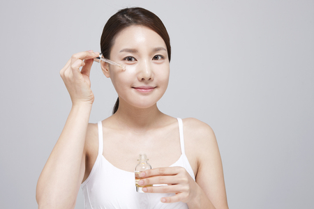 ample: Asian young woman applying ample serum on face isolated on white background