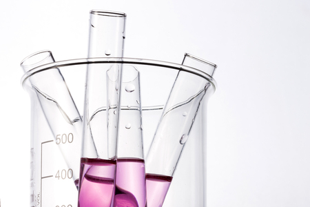 Four test tubes filled with red solution are in a beaker.