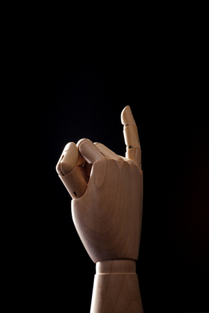 A wooden ball-jointed right hand isolated on black background makes a little finger promise with palm backward.