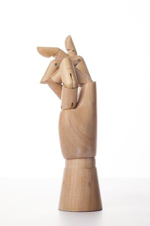 Una mano derecha articulada con bolas de madera aislada en el fondo blanco hace un dedo índice y un dedo medio doblado con la palma a un lado. Foto de archivo - 92674854