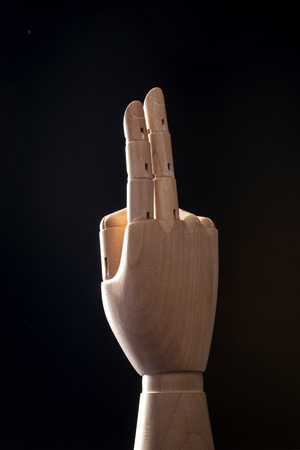 A wooden ball-jointed right hand isolated on black background makes an index finger and a middle finger the number two with palm backward. Stock Photo