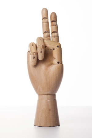 A wooden ball-jointed right hand isolated on white background makes an index finger and a middle finger the number two with palm forward.