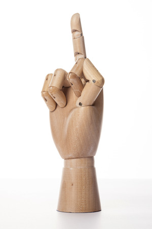 A wooden ball-jointed right hand isolated on white background makes a middle finger insult with palm to the side.