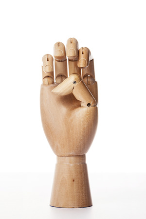 A wooden ball-jointed right hand isolated on white background shows bended fingers with palm forward. Stock Photo