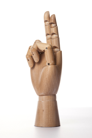 A wooden ball-jointed right hand isolated on white background makes an index finger and a middle finger the number two with palm to the side.