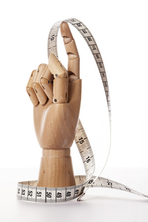 A wooden ball-jointed right hand isolated on white background makes an index finger the number one holding a tape measure with palm to the side.