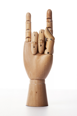 A wooden ball-jointed right hand isolated on white background makes the a thumb, a middle finger, and a ring finger bended holding a tape measure with a plam forward. Foto de archivo