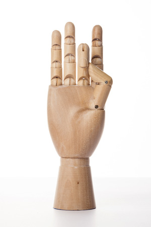A wooden ball-jointed right hand isolated on white background makes a thumb and a middle finger bended with palm forward.