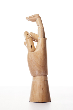 A wooden ball-jointed right hand isolated on white background makes an index finger and a middle finger bended with palm to the side. Stock Photo