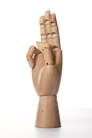 A wooden ball-jointed right hand isolated on white background makes index finger, middle finger, and ring finger the number three with palm to the side.