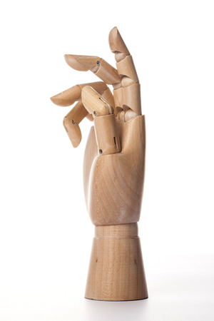 A wooden ball-jointed right hand isolated on white background makes a thumb, a ring finger, and a little finger bended with palm to the side.