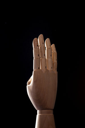 A wooden ball-jointed right hand isolated on black background makes index finger, middle finger, ring finger, and little finger the number four with palm backward.