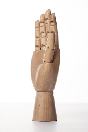 A wooden ball-jointed right hand isolated on white background shows a palm to the front with fingers spread.
