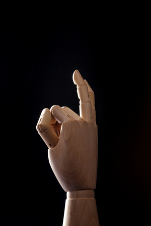 A wooden ball-jointed right hand isolated on black background makes a thumb, an index finger, and a middle finger folded with palm backward. Stock Photo