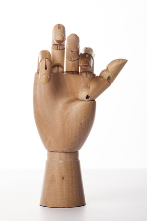 A wooden ball-jointed right hand isolated on white background makes an index finger, a middle finger, a ring finger, and a little finger bened with palm forward. Foto de archivo