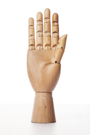A wooden ball-jointed right hand isolated on white background shows a palm forward with fingers spread.
