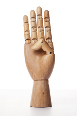 A wooden ball-jointed right hand isolated on white background makes index finger, middle finger, ring finger, and little finger the number three with palm forward. Foto de archivo