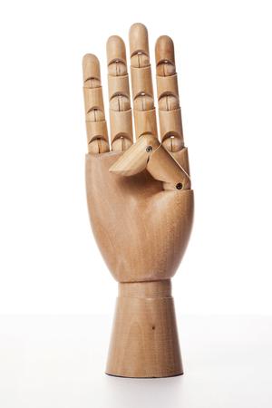 Una mano derecha articulada con bolas de madera aislada sobre fondo blanco hace que el dedo índice, el dedo medio, el dedo anular y el meñique el número tres con la palma hacia adelante. Foto de archivo - 92677191