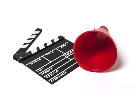 A film slate and a red plastic megaphone isolated on white background