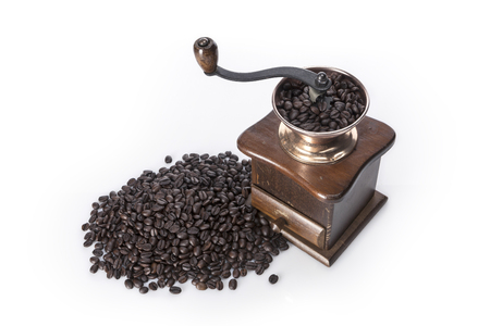 A brown wooden coffee grinder and coffee beans isolated on white background