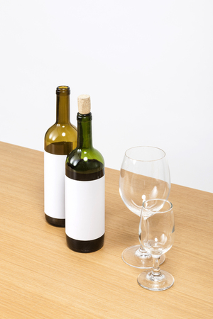 Two wine bottles and two wine glasses isolated on white background