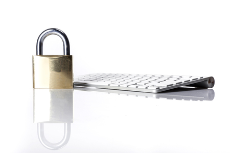 A metal lock isolated on white background stands on a white keyboard.