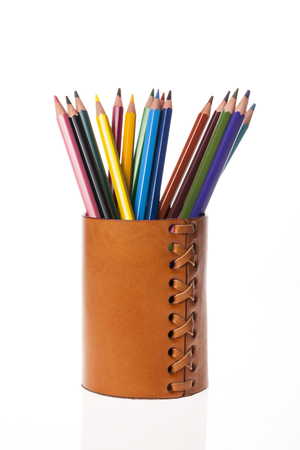 Colored pencils in a brown leather pen case isolated on white background