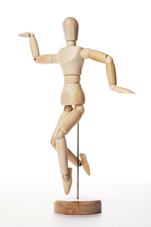 A wooden ball-jointed doll isolated on white background shows a person jumping to the side with arms stretched ourside and right leg back. Фото со стока