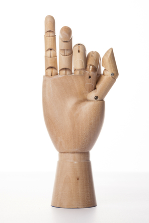 A wooden ball-jointed right hand isolated on white background makes an index finger and a middle finger bended with palm forward.