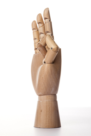 A wooden ball-jointed right hand isolated on white background makes a middle finger, a ring finger, and a little finger the number three with palm to the side.