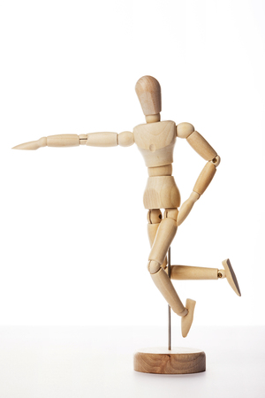 A wooden ball-jointed doll isolated on white background shows a person jumping to the side with right arm pointing forward.