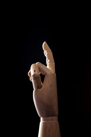 A wooden ball-jointed right hand isolated on black background makes a thumb, an index finger, and a middle finger folded with palm to the side.