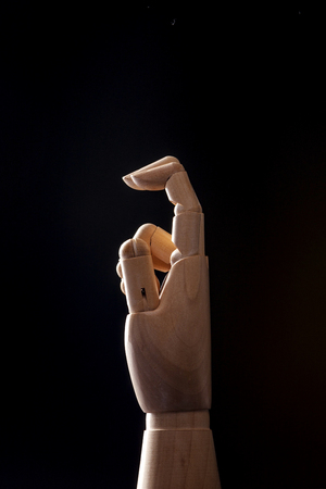A wooden ball-jointed right hand isolated on black background makes an index finger and a middle finger bended with palm to the side.