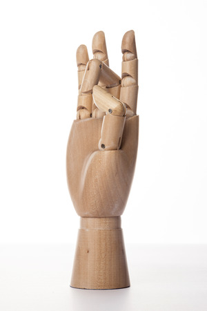 A wooden ball-jointed right hand isolated on white background makes a thumb and a middle finger bended with palm to the side. Foto de archivo