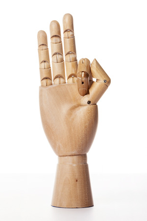 A wooden ball-jointed right hand isolated on white background makes a middle finger, a ring finger, and a little finger the number three with palm forward.